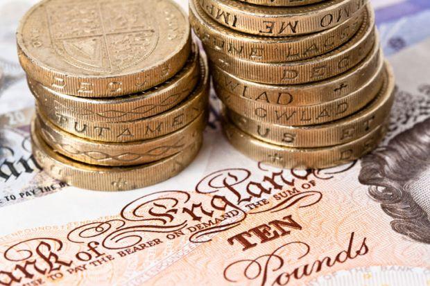 Pound coins stacked on ten pound note