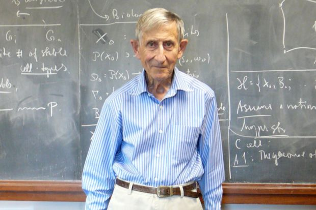 Professor Freeman Dyson standing in front of lecture hall blackboard