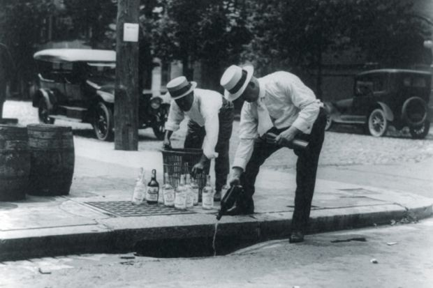 Men pouring alcohol down drain during prohibition