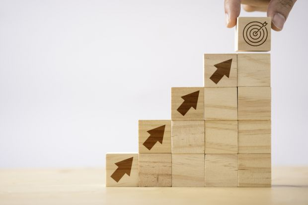 Wooden bricks with arrows pointing upwards towards a target, symbolising promotion