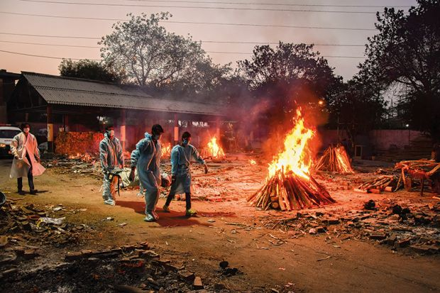 Workers carry the body of a person who has died of Covid-19 as funeral pyres burn during a mass cremation at a crematorium, New Delhi, 2021/05/03