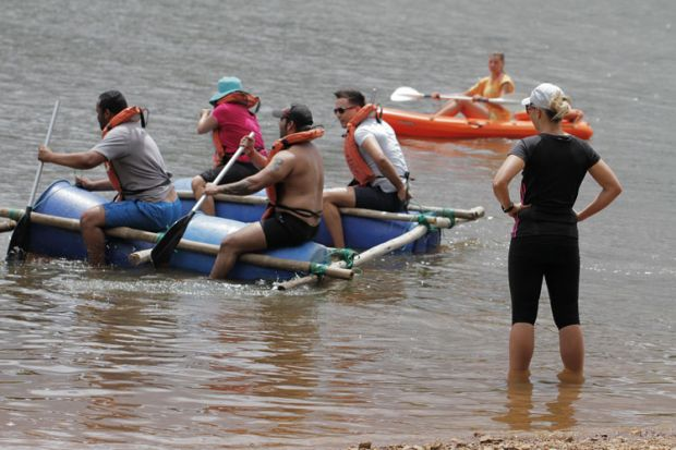 People paddling on a makeshift raft