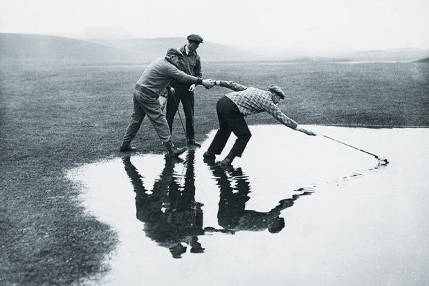 men reaching in pond