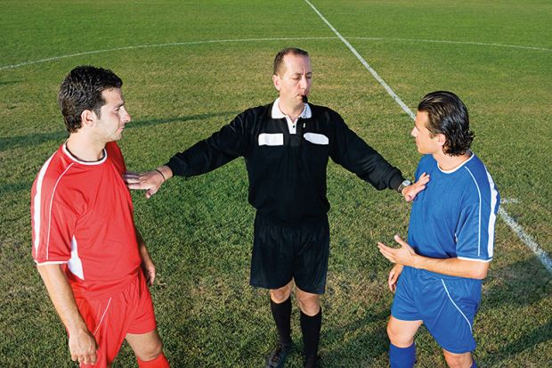 Referee between two footballers
