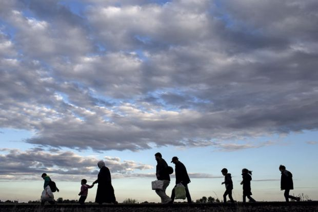 Refugees walking across a field