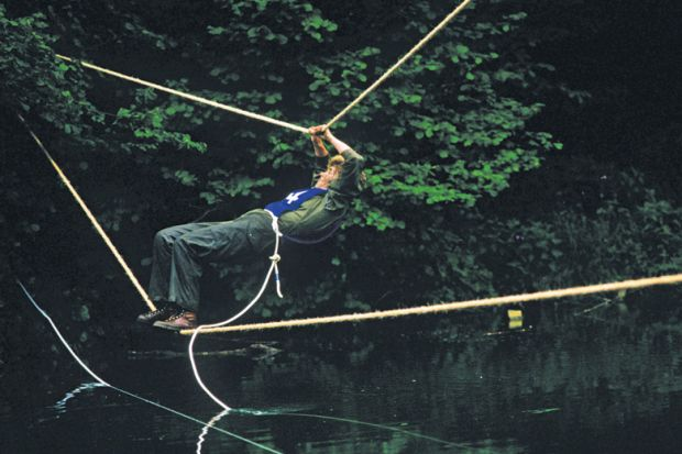 Man crosses river via rope