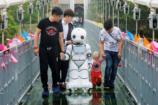 People with robot on bridge