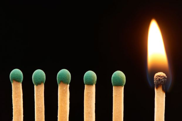Row of green matches, one burning
