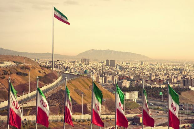 Row of Iran flags against Tehran skyline