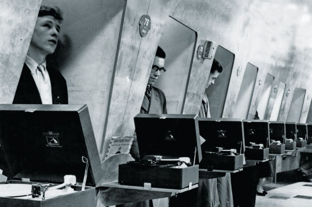 Row of men listening to vinyl records in turntable booths