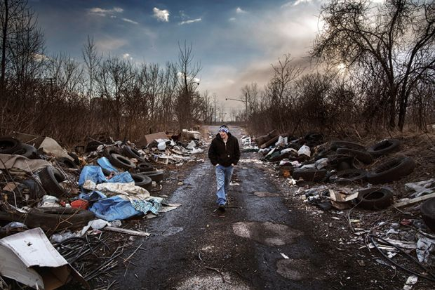Man walks through a rubbish strewn road