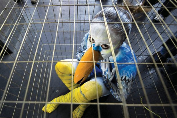 Sad young woman dressed as bird in cage
