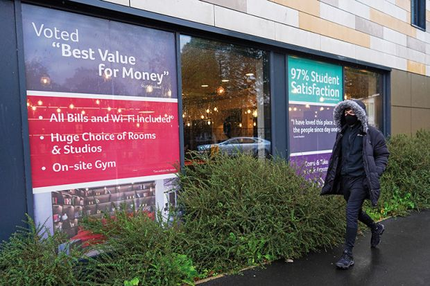 Man walks past office renting student accommodation illustrating education's value for money
