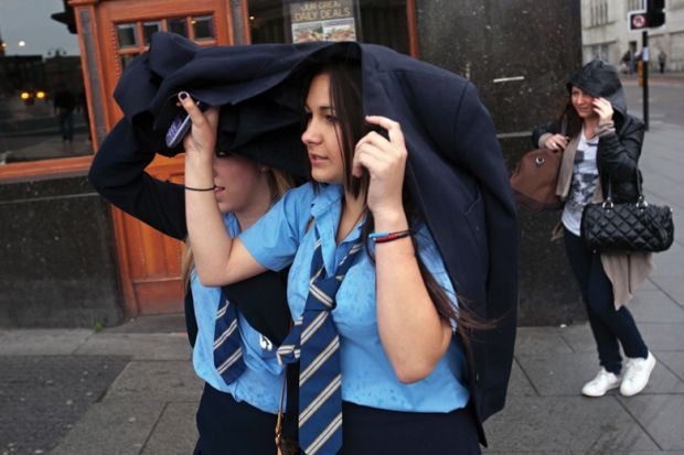 Schoolgirls shelter heads from rain, Liverpool