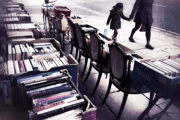 People walk past second hand books for sale