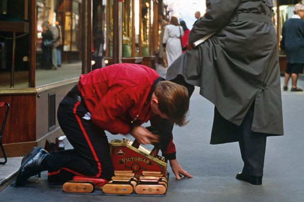 Shoeshine boy polishing man's shoes