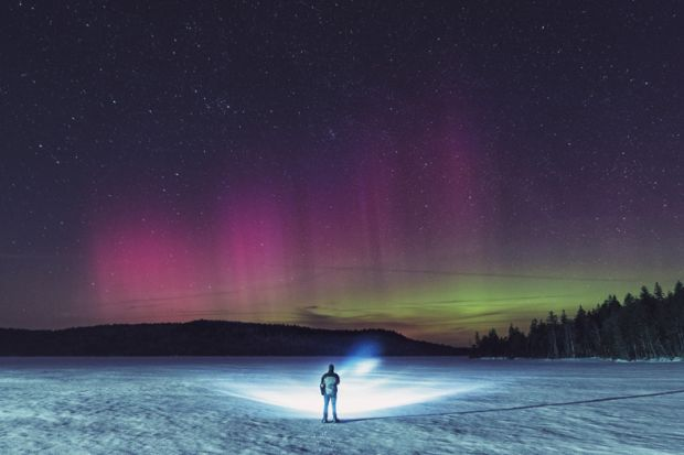 A man standing in the snow looking at the Northern Lights