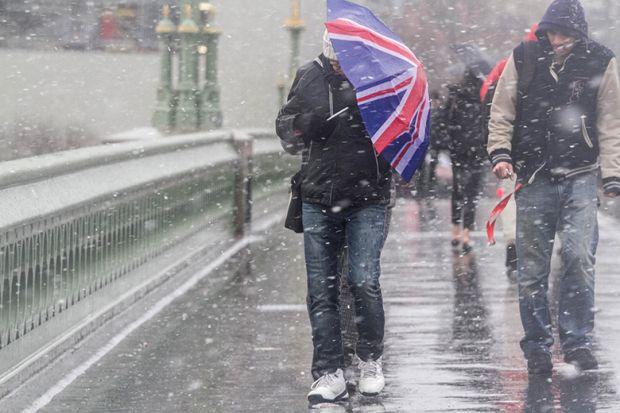 Man crosses bridge with Union Jack umbrella as snow falls