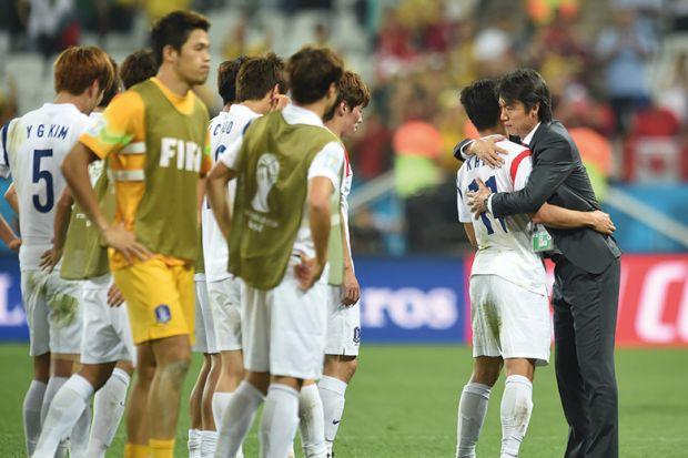 South Koreas football coach hugs one player