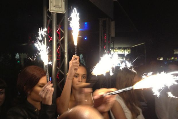 Women holding sparklers at party