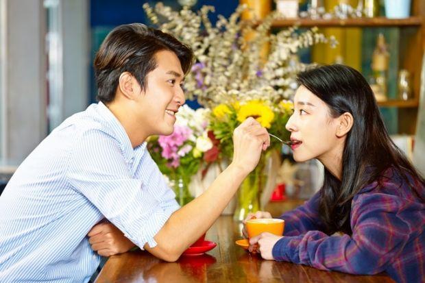 A man spoon-feeding a woman