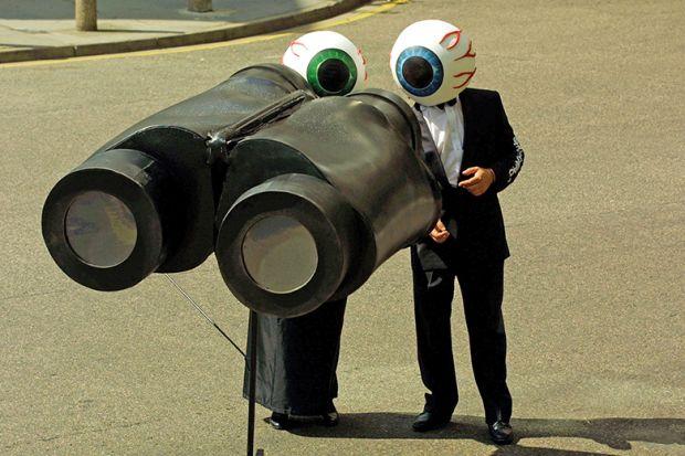 People dressed as eyeballs watch through giant pair of binoculars