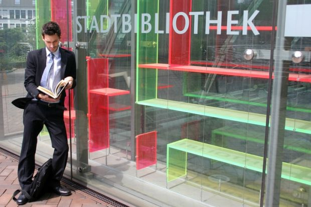 A suited man reads a book outside an empty bookshop
