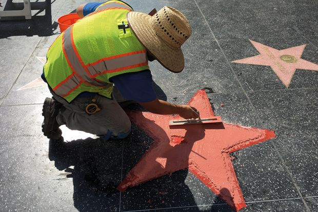 A worker repairs a star on the Hollywood Walk of Fame