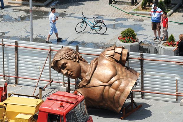 People walk past a bronze component of a statue