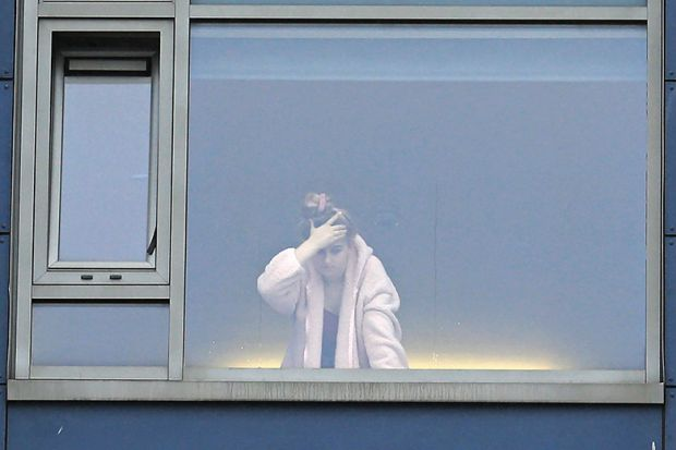 A student at the window in a university halls of residence