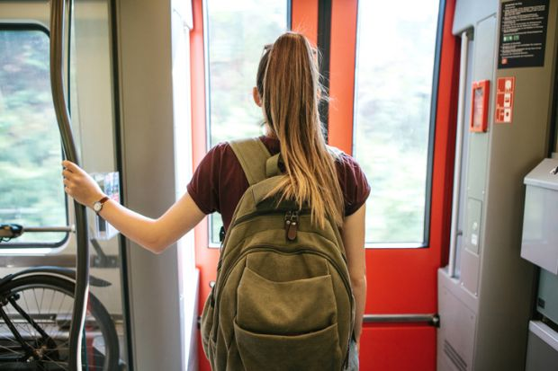 student with a backpack waiting for the train to stop to go outside