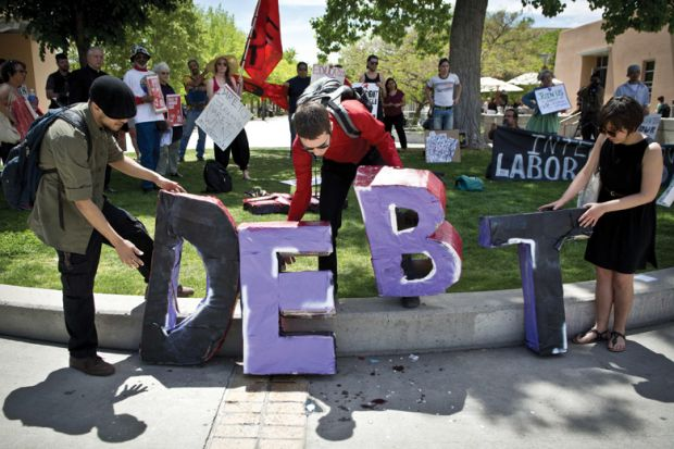 Students holding letters spelling 'Debt', University of New Mexico