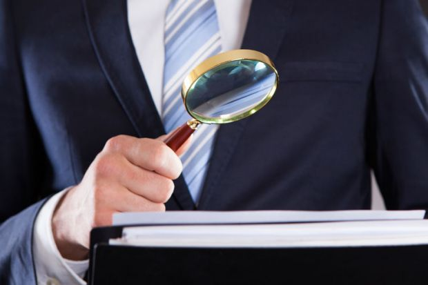Suited businessman examining paperwork with magnifying glass