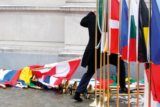 Suited man setting up row of international flags