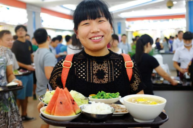 Sun Yat-sen University student holding tray of food
