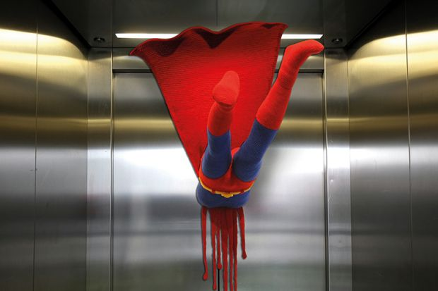 Superman flying into a closed lift door