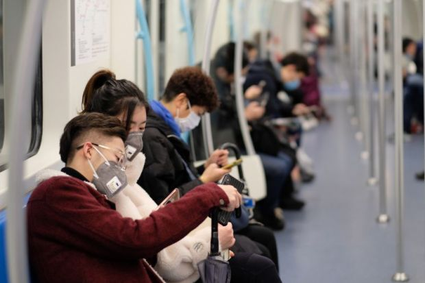 People on subway wearing surgical masks