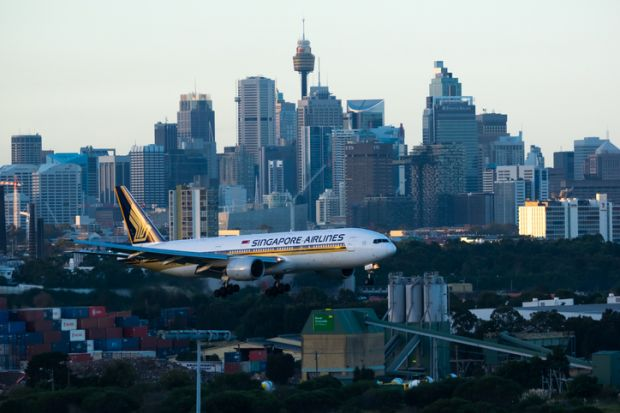 Sydney Australia May 13, 2014 Boeing 777 wearing Singapore Airlines livery approaching for landing at Kingsford Smith airport at Dusk , with the city Skyline in the background