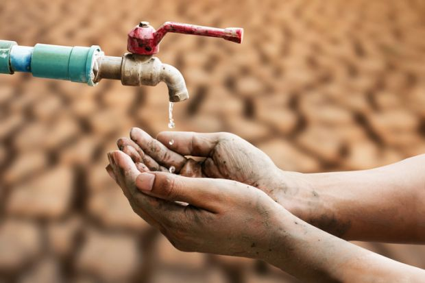 A hand under a tap dripping water, symbolising cuts to the UK's ODA spending