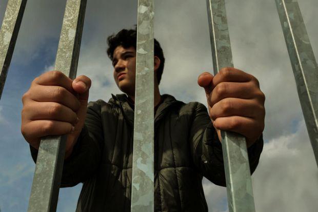 Teenage boy hands holding strong iron bar