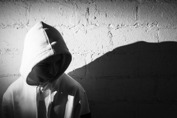 Teenage boy with his hood up against a white brick wall