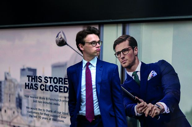 A businessman pauses next to a closed shop poster featuring a similar man also wearing a blue suit and enjoying leisure time on the golf course