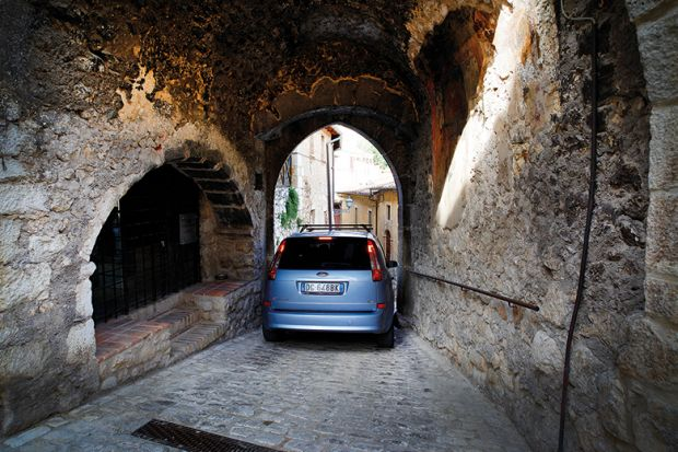 Car squeezing through a narrow arch