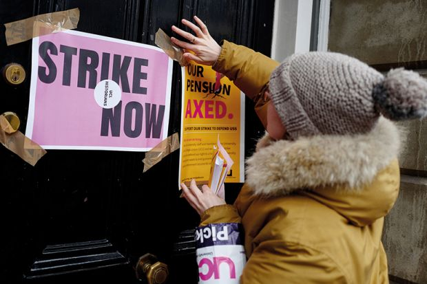 A demonstrator sticks a poster to a door as members of the University and College Union (UCU) stand at a picket line in protest against university lecturers' pay and pensions, outside of an entrance at University College London (UCL) in central London