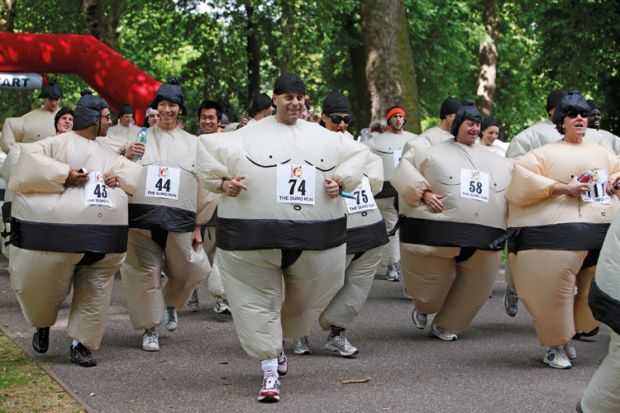 Men and women compete in the quirky annual Sumo Run held on a weekend in June, in Battersea Park, in London, England