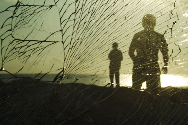 Silhouettes of people behind broken glass
