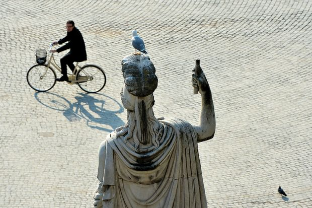 A man cycling past a statue in Rome