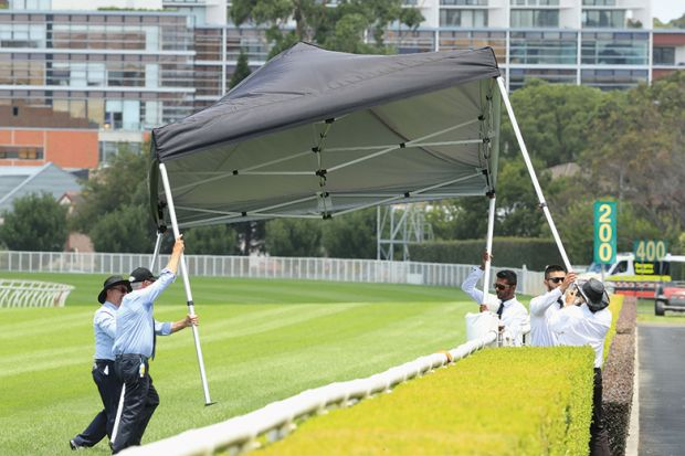 People stop a gazebo from blowing away