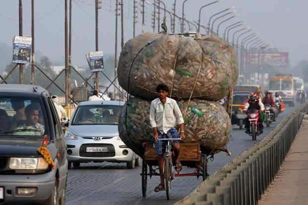 An Indian rickshaw puller transports discarded plastic bottles in Allahabad