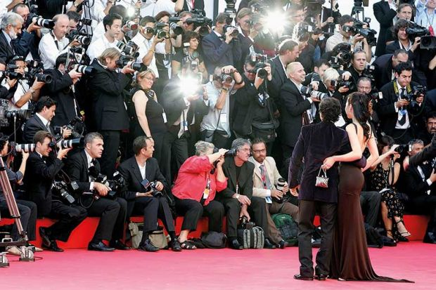 Paparazzi taking photos of stars on red carpet